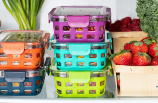 Various food containers containing fresh produce, on a fridge shelf.