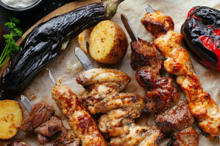 Various grilled meat including chicken and beef kebabs, potatoes, a red pepper and aubergine.